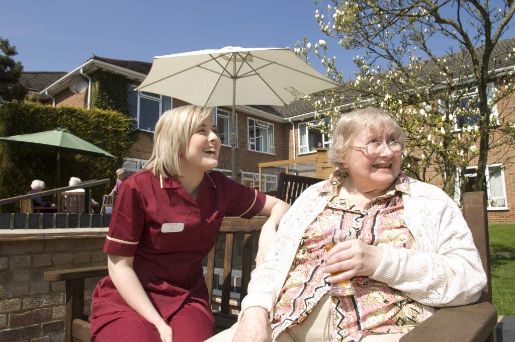 Resident enjoying sun in garden with carer